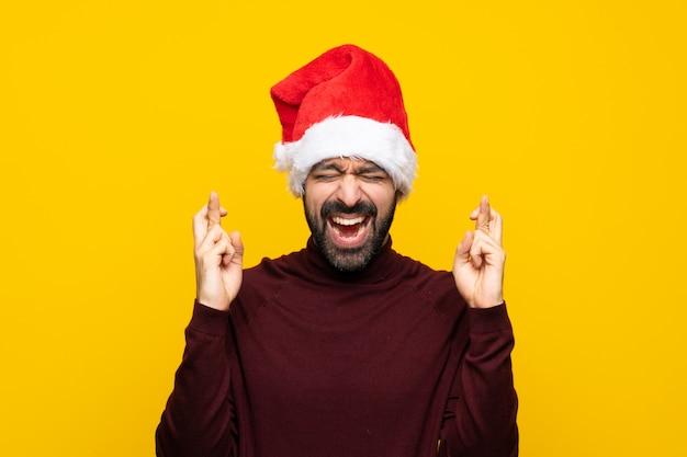 Homem com chapéu de natal isolado muro amarelo com dedos cruzando