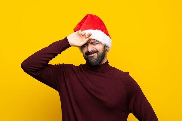 Homem com chapéu de natal isolado muro amarelo com expressão cansada e doente