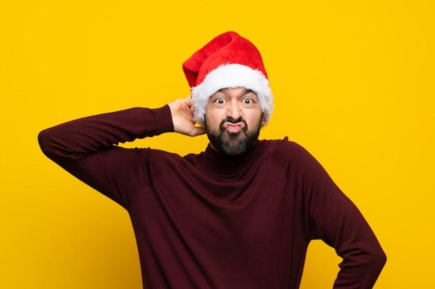 Homem com chapéu de natal isolado muro amarelo tendo dúvidas