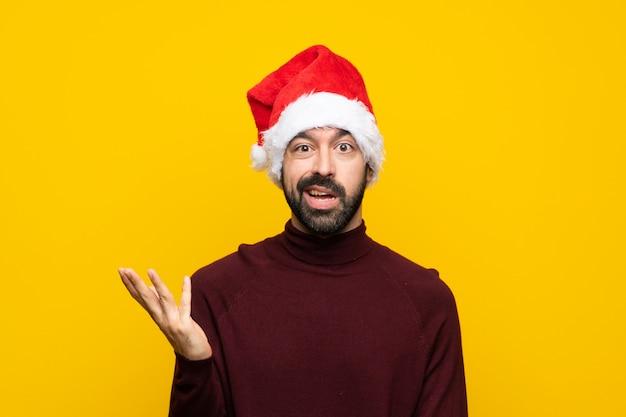 Homem com chapéu de natal isolado parede amarela fazendo gesto de dúvidas
