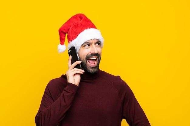 Homem com chapéu de natal isolado parede amarela mantendo uma conversa com o telefone móvel
