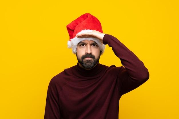 Homem com chapéu de natal isolado parede amarela olhando longe com a mão para procurar algo