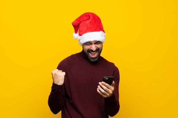 Homem com chapéu de natal sobre fundo amarelo isolado com telefone em posição de vitória