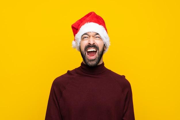 Homem com chapéu de natal sobre fundo amarelo isolado, gritando para a frente com a boca aberta