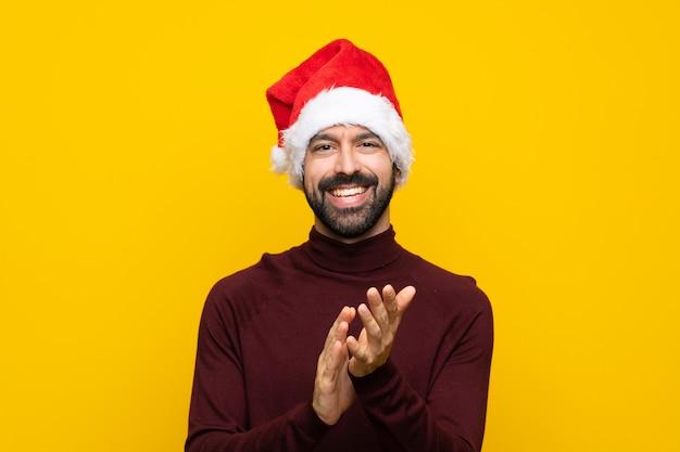 Homem com chapéu de natal sobre parede amarela isolada aplaudindo após apresentação em uma conferência