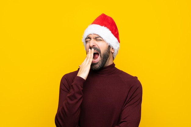 Homem com chapéu de natal sobre parede amarela isolada, bocejando e cobrindo a boca aberta com a mão