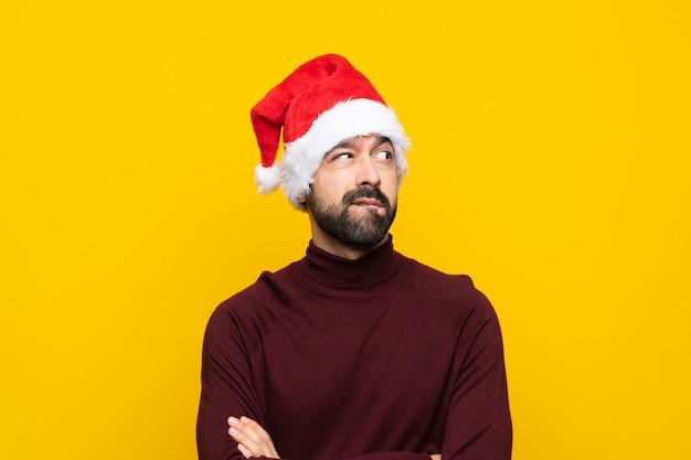 Homem com chapéu de natal sobre parede amarela isolada com confundir a expressão do rosto
