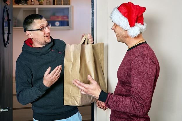 Homem com chapéu de papai noel dá ao amigo o pacote que tem presente dentro.