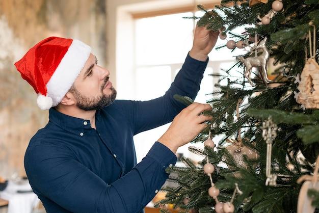 Homem com chapéu de papai noel decorando uma árvore