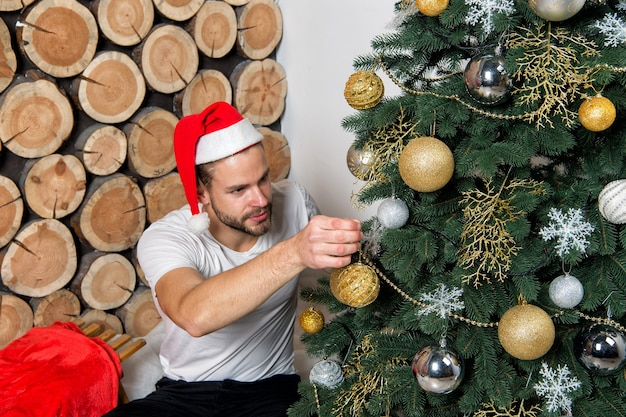 Homem com chapéu de papai noel decorar a árvore de natal com bolas, flocos de neve, guirlandas em fundo de toras de madeira. natal, ano novo, véspera, celebração de feriados. decorações e ornamentos festivos