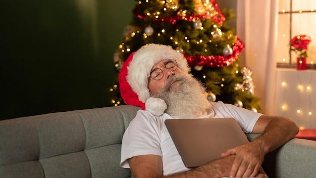 Homem com chapéu de papai noel dormindo em casa enquanto segura seu laptop
