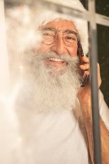 Homem com chapéu de papai noel falando no smartphone pela janela