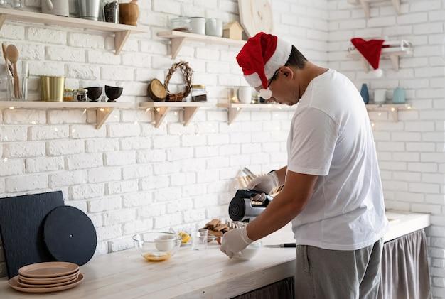 Homem com chapéu de papai noel fazendo merengue em uma mesa de madeira branca com espaço de cópia