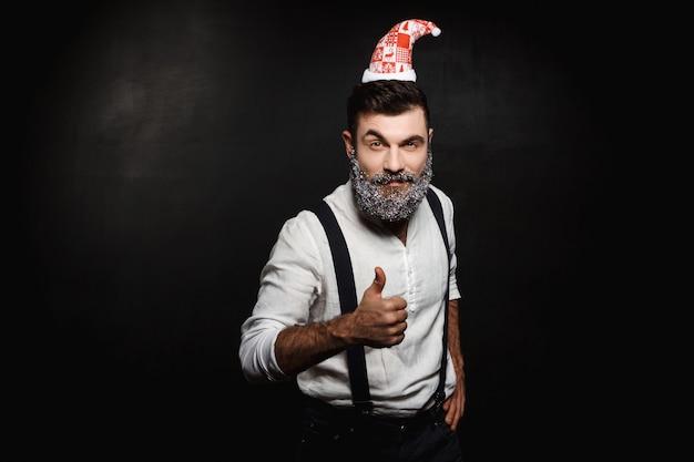 Homem com chapéu de papai noel mostrando bem sobre preto.