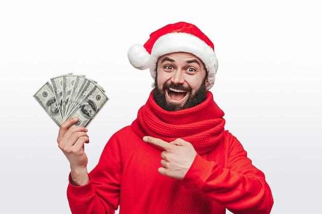 Homem com chapéu de papai noel mostrando monte de dinheiro