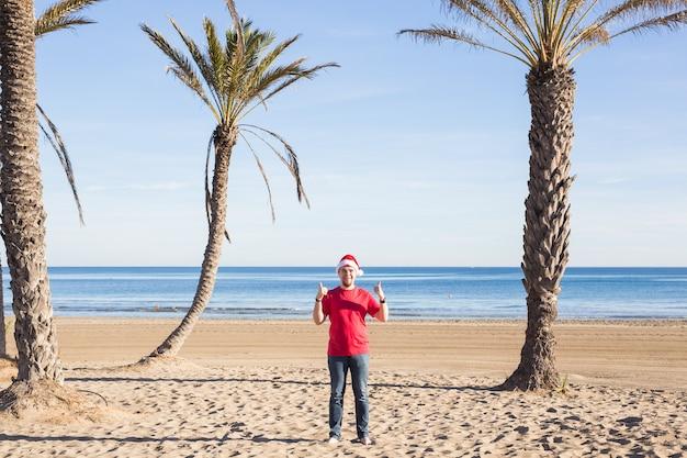 Homem com chapéu de papai noel mostrando o polegar para cima na praia