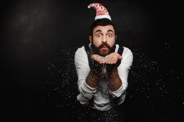 Homem com chapéu de papai noel soprando glitter prata sobre preto.