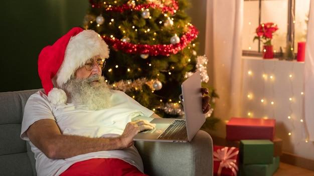 Homem com chapéu de papai noel usando laptop no sofá em casa