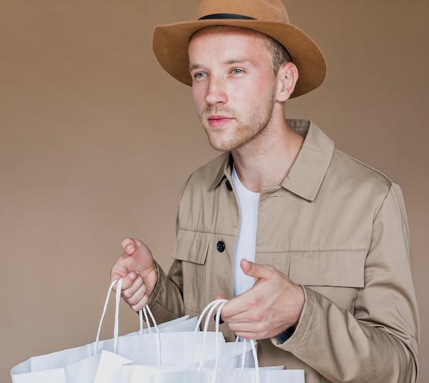 Homem com chapéu marrom e redes de compras