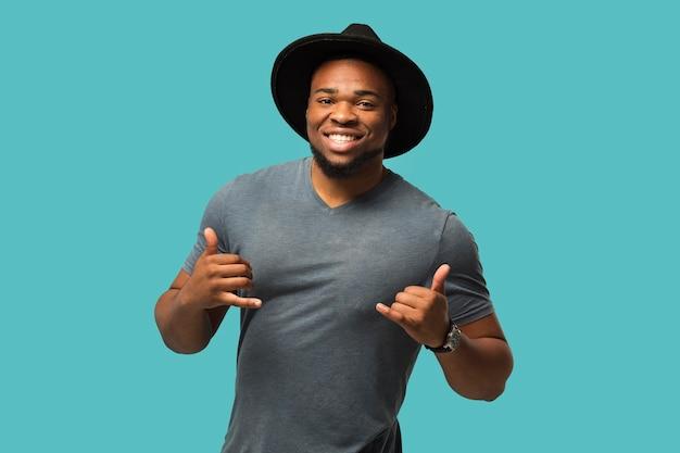 Homem com chapéu mostrando sinal de chamada