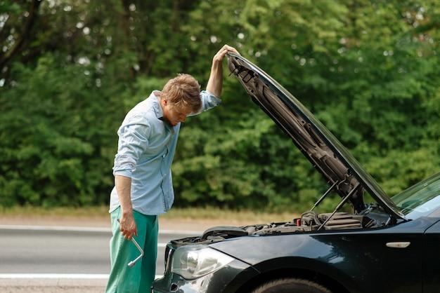 Homem com chave de roda em pé no capô aberto, avaria do carro.