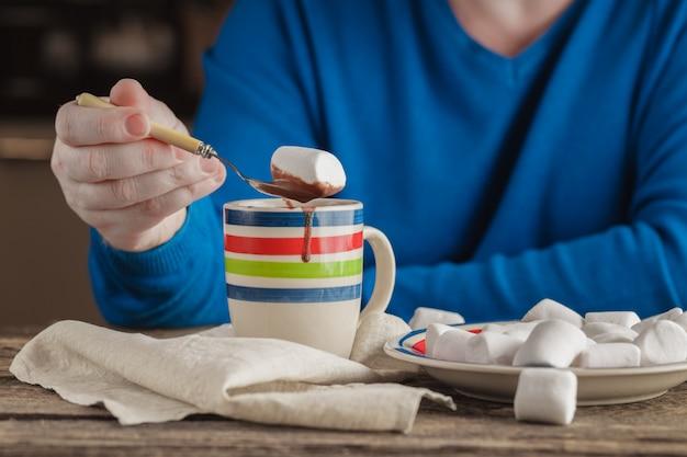 Homem com chocolate quente caneca com marshmallows, bebida de natal de inverno