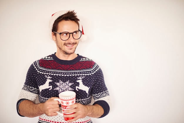 Homem com chocolate quente em frente a parede