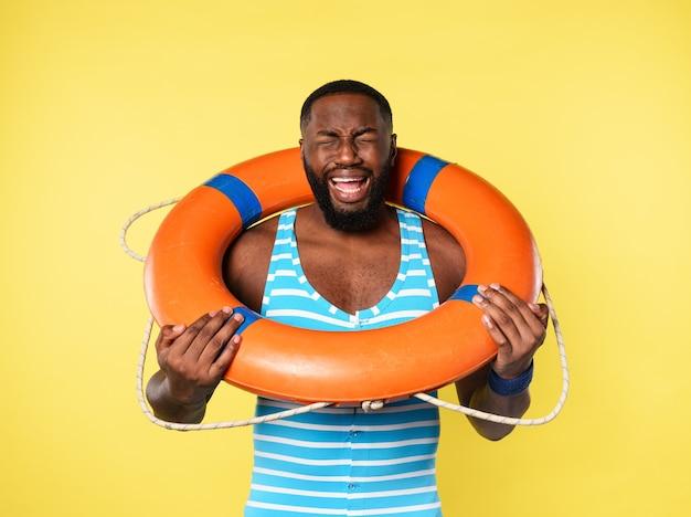 Homem com cinto de salvação tem medo de nadar. fundo amarelo