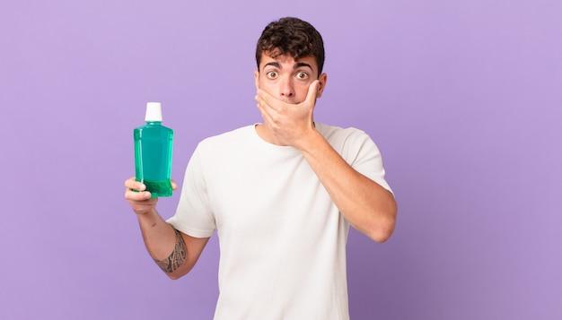 Homem com colutório cobrindo a boca com as mãos com uma expressão chocada e surpresa, mantendo um segredo ou dizendo oops