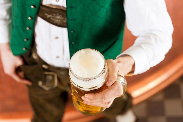 Homem com copo de cerveja na cervejaria