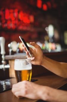 Homem com copo de cerveja, usando telefone celular no balcão