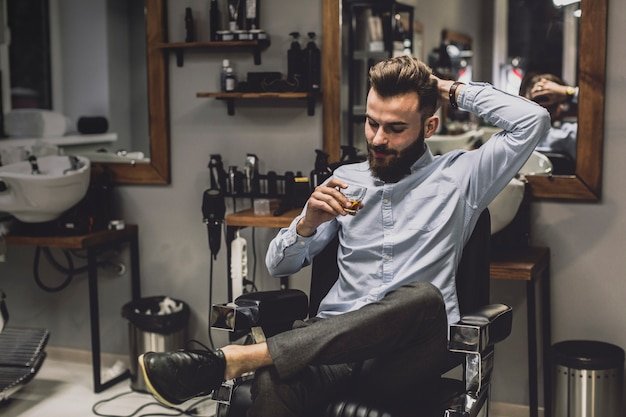 Homem com copo de licor na barbearia