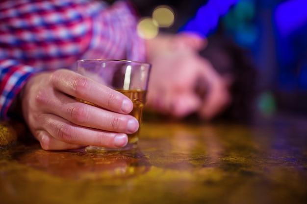 Homem com copo de uísque deitado no balcão de bar