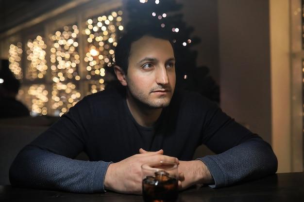 Homem com copo de uísque no bar à noite