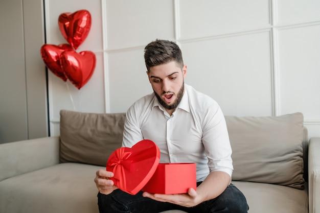 Homem com coração em forma de presente vermelho na caixa de presente, sentada no sofá com balões em casa