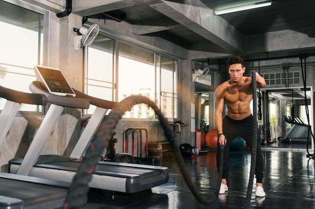 Homem com corda de batalha fazendo exercício.