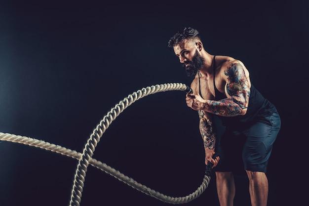 Homem com corda em treinamento funcional