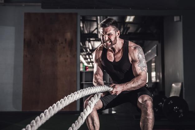 Homem com corda no ginásio de treino funcional