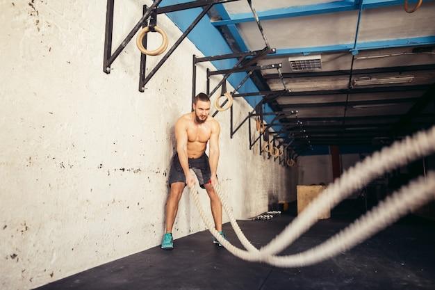 Homem com cordas de batalha exercitando no ginásio de fitness
