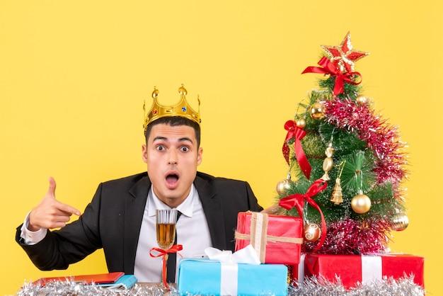Homem com coroa sentado na mesa com o dedo apontando