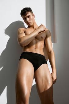 Homem com corpo musculoso e musculoso em shorts escuros com fundo claro