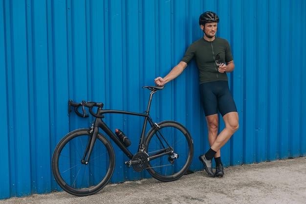 Homem com corpo musculoso em pé com bicicleta perto da parede azul