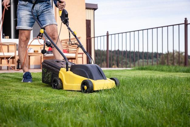 Homem com cortador de grama, grama verde