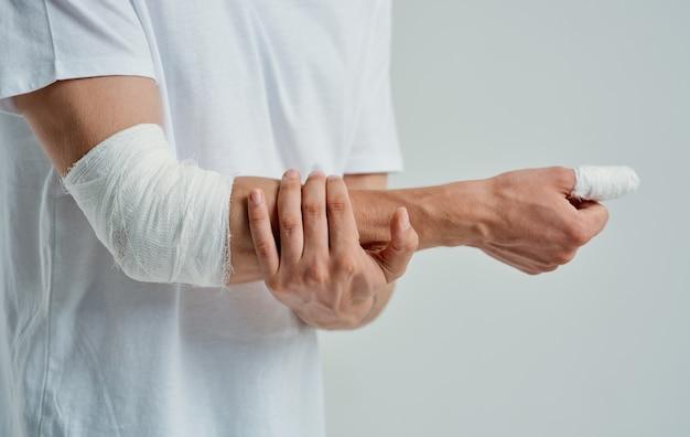 Homem com cotovelo enfaixado e remédio para lesões nos dedos