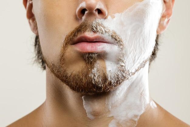 Homem com creme de barbear aplicado no rosto