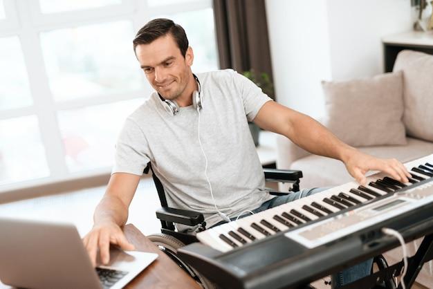 Homem com deficiência compondo música com piano elétrico.