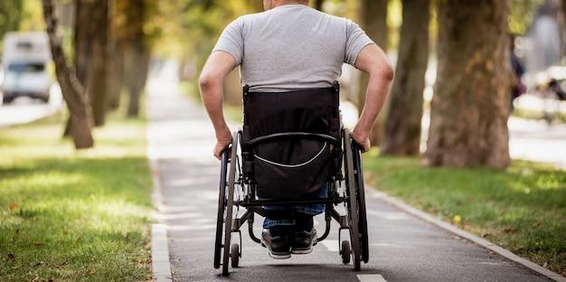 Homem com deficiência em cadeira de rodas a pé no beco do parque.