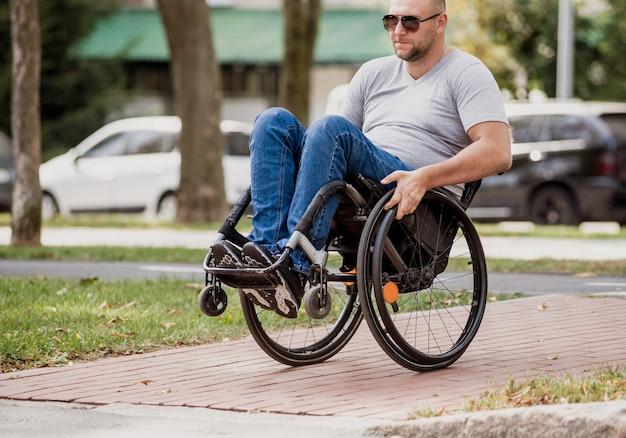 Homem com deficiência em cadeira de rodas, atravessando a rua.