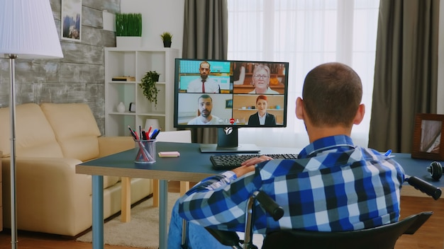 Homem com deficiência em cadeira de rodas durante uma videochamada com colegas.