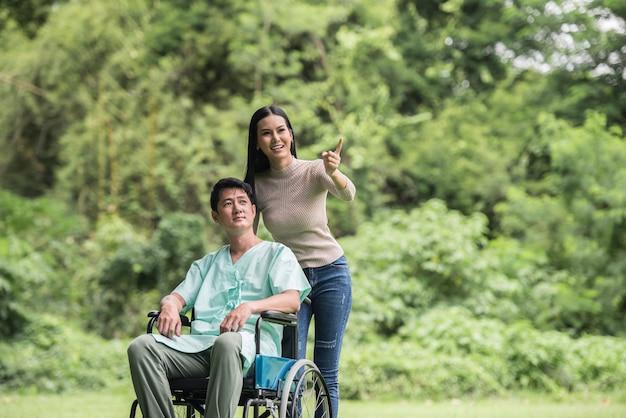 Homem com deficiência em cadeira de rodas e namorada no parque